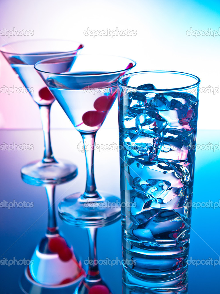 Two glasses of martini with red cherries and a glass of clear cocktail — Stock Photo #10968412