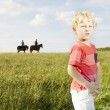 Stock Photo: Young blonde boy standing in a grassy field