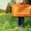 Man with travel bag standing on green lawn - Stock Photo