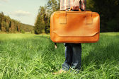 Man with travel bag standing on green lawn — Stock Photo