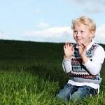 Impish little boy kneeling in green field — Stock Photo