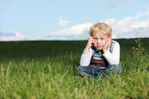 Glum little boy sitting in grass — Stock Photo