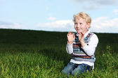 Impish little boy kneeling in green field — Stock Photo