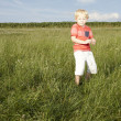 Small blonde boy in grassy field — Stock Photo