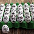 White eggs and  many funny faces — Stock Photo