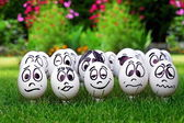 White eggs and many funny faces, garden party — Stock Photo