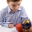 Serious boy writes in a notebook on a table - Stock Photo