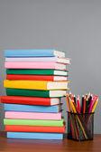 Lápices de colores y una pila de libros — Foto de Stock