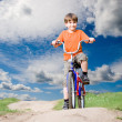 Stock Photo: Boy on bicycle on background of blue sky