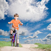 Boy on a bicycle on a background of blue sky — Stock Photo