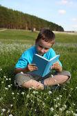 Pojke läser en bok — Stockfoto