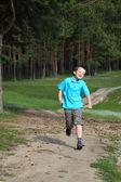 Happy boy runs near the forest — Stock Photo