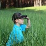 Boy sitting in tall grass — Stock Photo