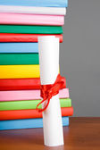 Diploma and stack of books — Stock Photo