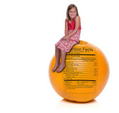 Girl Sitting on Orange with Nutrition Label — Stock Photo
