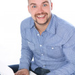 Handsome smiling guy with laptop — Stock Photo