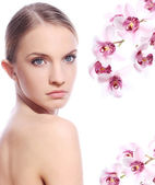 Beautiful woman and orchid flowers — Stock Photo