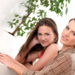 Two beautiful sisters relax at home — Stock Photo