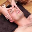 Man enjoying face massage — Stock Photo