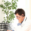 Young doctor working in his office — Stockfoto