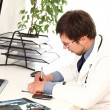 Young doctor working in his office — Stock Photo