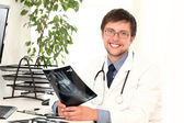Young doctor viewing xray — Stock Photo