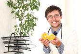医者の手の中のオレンジと笑みを浮かべてください。 — ストック写真