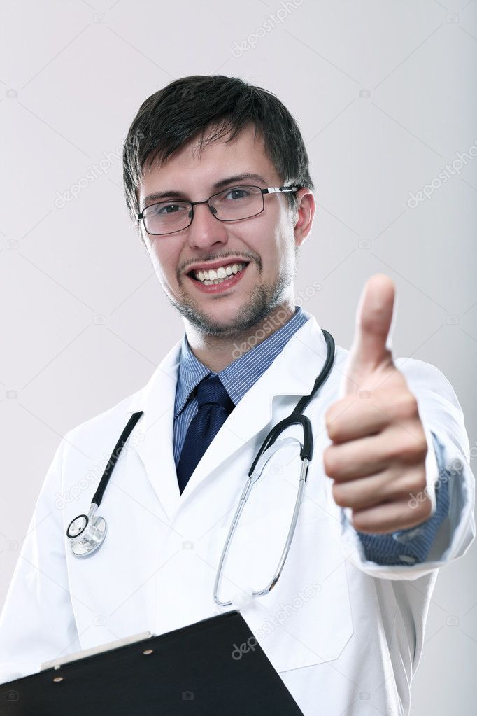 Young smiling doctor with thumbs up over gray background — Foto Stock #11121541