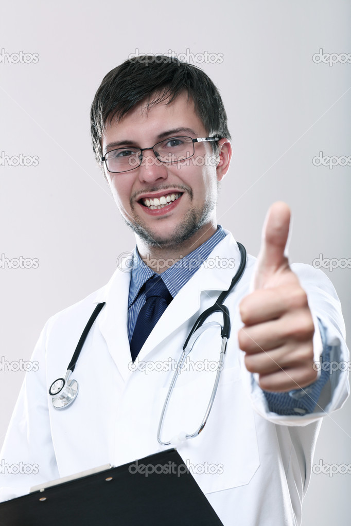 Young smiling doctor with thumbs up over gray background  Stockfoto #11121541