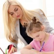 Older sister is teaching younger sister how to draw — Stock Photo