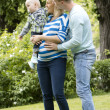 Young and happy family in the park — Stock Photo #11357412