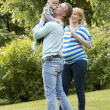 Young and happy family in the park — Stock Photo #11357420