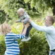 Young and happy family in the park — Stock Photo #11357431