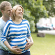 Pregnant woman and her husband in the park — Stock Photo