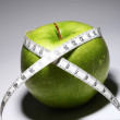 Fresh green apple with measure tape — Stock Photo