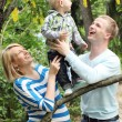 Young and happy family in the park — Stock Photo