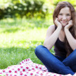 Portrait of young smiling girl in the park — Stock Photo