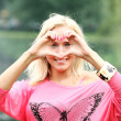 Stock Photo: Happy blonde forming heart with her hands