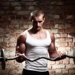 Young muscular guy training biceps with barbell — Stok fotoğraf