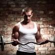 jonge gespierde kerel opleiding biceps met barbell — Stockfoto