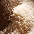 White rice grains on sack cloth — Stock Photo
