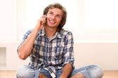 Człowiek siedzi na podłodze i rozmawia przez telefon — Zdjęcie stockowe