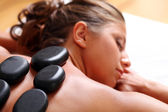 Woman enjoying a hot stone massage — Stock Photo