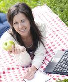 Glad kvinna anläggningen grönt äpple — Stockfoto