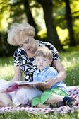 Babcia czytanie książki do wnuka — Zdjęcie stockowe