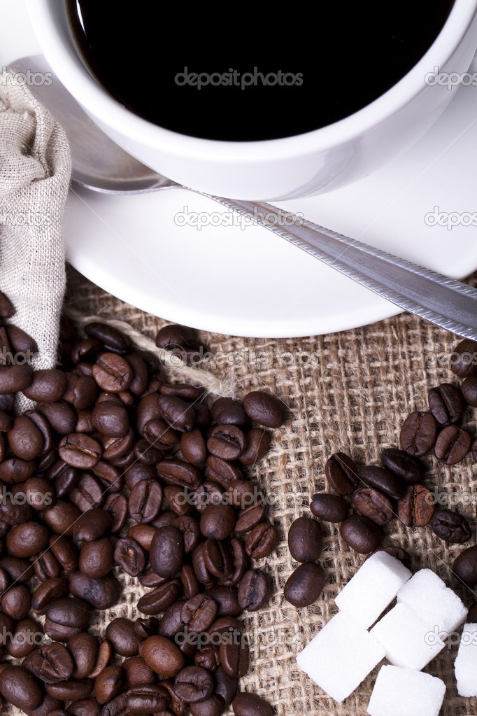 Cup of hot coffee over cloth sack — Stock Photo #11834010