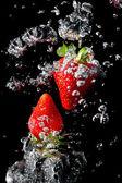 Dwa truskawki w wodzie z pęcherzyków powietrza — Zdjęcie stockowe