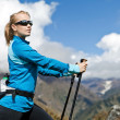 Woman nordic walking and exercising in mountains — Stock Photo