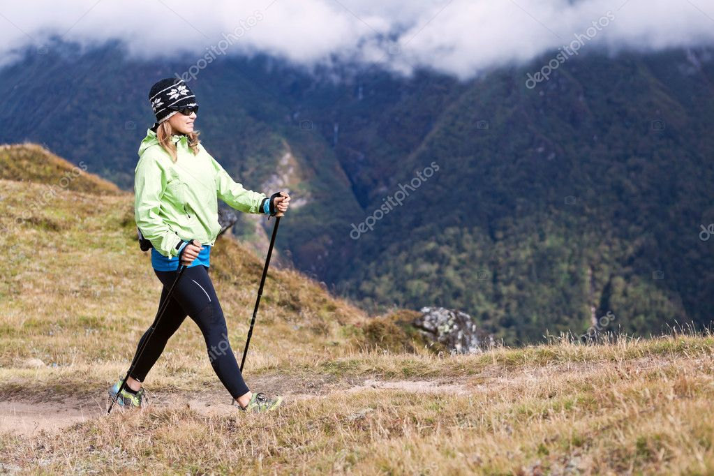 Young woman nordic walking in mountains, fitness and exercise outdoors. — Stock Photo #11357570