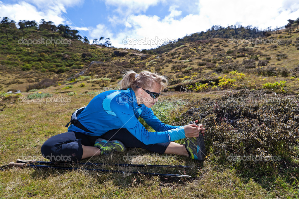 Young woman exercising and stretching in mountains, nordic walking in summer — Stock Photo #11357575